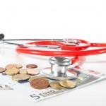 Geld und Stethoskop auf einem weißen Tisch