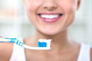 Frau hält mit Zahnpasta bestrichene Zahnbürste vor sich