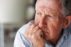 Grübelnder älterer Mann stützt seinen Kopf auf die Hand auf