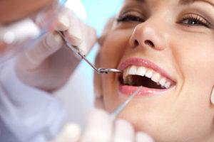 Frau wird vom Zahnarzt untersucht