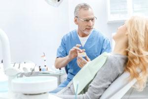 Zahnarzt zeigt Patientin einen Gebissabdruck